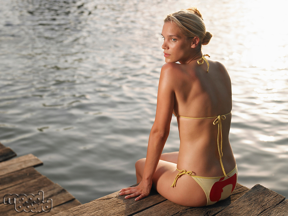 Young woman sitting on jetty looking over shoulder back view