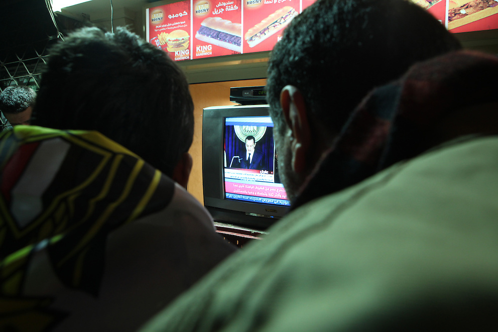 Pro-democracy protesters at a cafe in downtown Cairo near Tahrir Square closely watch a speech by then President Hosni Mubarak on 1 February. .