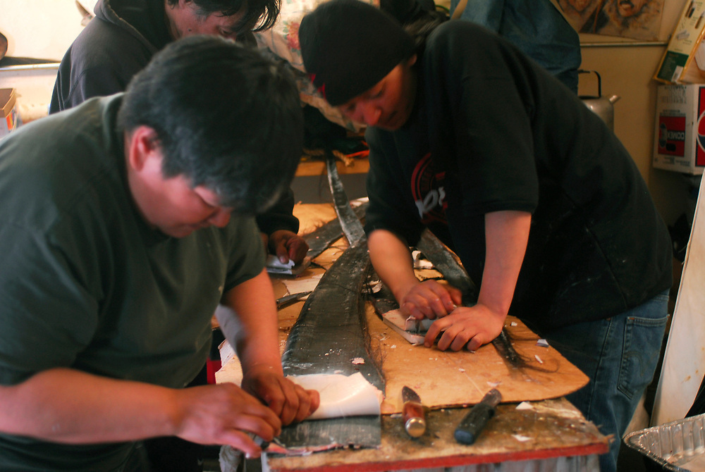 "Barrow, Alaska. After David Leavitt's Crew got a 34ft7"" whale, the crew prepaires for serving on the feast at the captain's house. In this image crewmembers are pulling the whale gums out of the baleen for serving it too. This whale was the fourth landed whale of this Spring season. May 2nd 2007."
