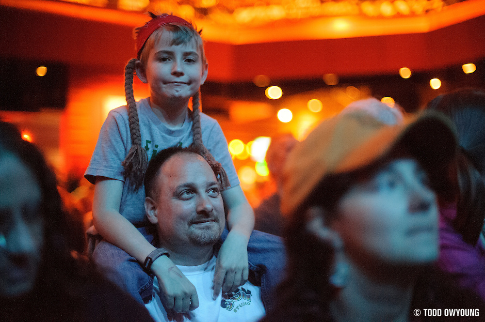 A young Willie Nelson fan wearing the singer's iconic red bandana and braids.