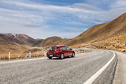 red car travelling through Lindis Pass Otago New Zealand