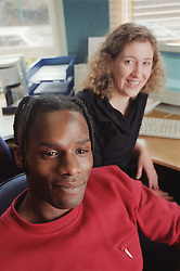 Two support workers sitting in office of Young Persons' Resettlement hostel,
