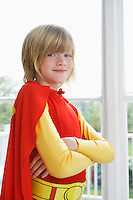 Portrait of boy (7-9) with arms crossed wearing superhero costume smiling