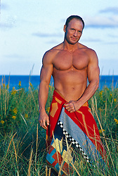 Shirtless man standing in a field with a blanket around his waist