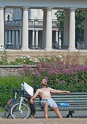 ©Licensed to London News Pictures 12/08/2020             Greenwich, UK. A man sitting on a bench enjoying the warm weather. The hot heatwave weather continues in London and the South East today with people out and about in Greenwich park,Greenwich, London. Photo credit: Grant Falvey/LNP