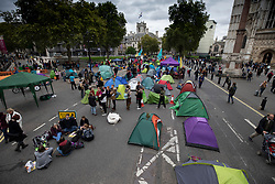 © Licensed to London News Pictures. 07/10/2019. London, UK. Extinction Rebellion activists erect tents in the road outside Westminster Abbey in central London. Activists are converging on Westminster blockading roads in the area for at least two weeks calling on government departments to 'Tell the Truth' about what they are doing to tackle the Emergency. Photo credit: Peter Macdiarmid/LNP