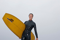 Surfer carrying surfboard on beach low angle view portrait