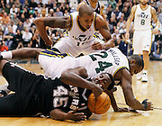 Spurs forward DeJuan Blair (45) and Jazz forward Paul Millsap (24) fall to the court while going after a loose ball as Jazz guard Raja Bell (19) assists during the first half of an NBA basketball game in Salt Lake City, Wednesday Jan. 26, 2011. (AP Photo/Colin E Braley)