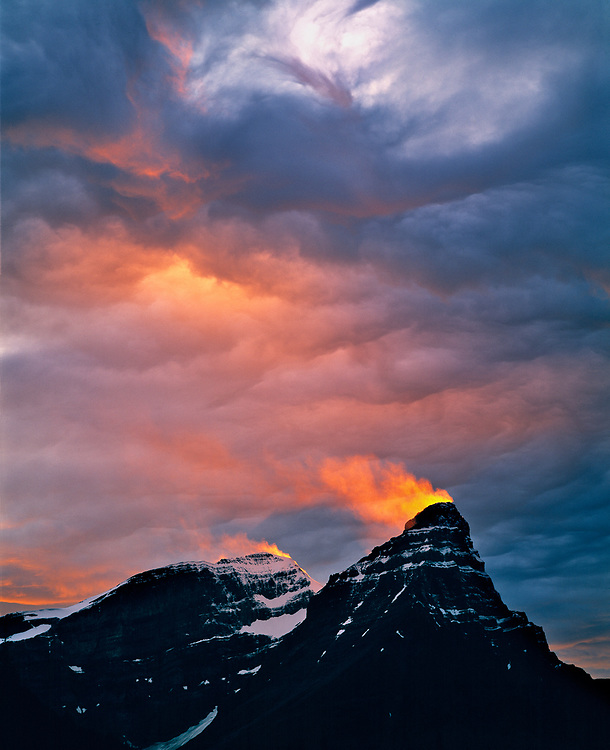 A golden shaft of sunset light ignites a snow plume blowing from the summit of Mount Chephren, in Banff National Park, Alberta, Canada. ©Ric Ergenbright