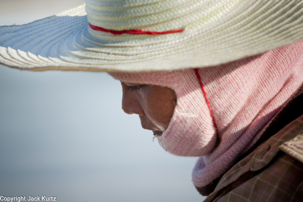 Mar 23, 2009 -- SAMUT SONGKHRAM, THAILAND: Salt workers wear hats and scarves to protect them from the sun and salt on salt farms near Samut Songkhram. The average daytime high in the area is about 34 Celsius (93 degrees F), with humidity near 100 percent. The salt farms between Samut Sakhon and Sumat Songkhram are Thailand's largest salt producing region. Salt is typically harvested for about six months of the year. The fields are prepared for salt farming as soon as the rainy season ends. First the fields are tamped down so they hold water, then they are flooded with salt water from either the Gulf of Siam or the Mae Khlong River (both are salty). After about two months, the first harvest is ready. The fields are drained and the salt picked up from the fields. Then the fields are flooded again and the process repeated. As the season goes on and the fields become saltier, the amount of time they are flooded is reduced till the end of the season when they may only be flooded for two or three days. Most of the workers in the salt fields are migrant workers from Isaan, an impoverished region in the northeast of Thailand. Once the rainy season starts and it's no longer possible to harvest salt the workers go home to work their small farms. The workers are paid based on the amount of salt their crew harvests.    Photo by Jack Kurtz