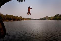 a boy jumping in Angkor lake