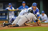 New York Yankees base runner Brett Gardner (left) gets tagged out trying to score on a wild pitch by Kansas City Royals catcher Salvador Perez (center) during the second inning at Kauffman Stadium.