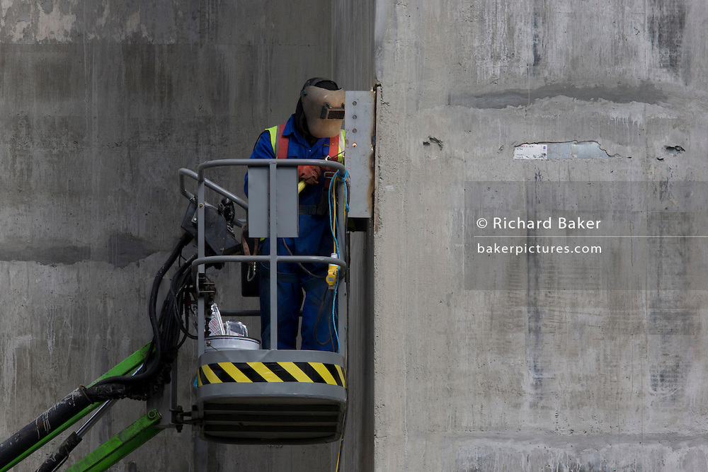 A welder works high up from the ground from the safety of a hydraulic platform on the side of a lift shaft being constructed on a large development project on London Wall in the City of London, the capital's financial district - also known as the Square Mile. With the visor of his helmet lit by the glow from his acetylene torch, the man leans towards the detail of this close-up contact job. Oxy-fuel welding (commonly called oxyacetylene welding, oxy welding, or gas welding in the U.S.) and oxy-fuel cutting are processes that use fuel gases and oxygen to weld and cut metals, respectively.
