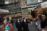 NAPLES, ITALY - 25 November 2013: Two nuns walk by via San Gregorio Armeno, a street known for its shops selling Naples' famous Christmas crèches and figurines, in Naples, Italy, on November 25th, 2013.