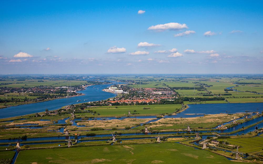Nederland, Zuid-Holland, Kinderdijk, 12-06-2009; Molens aan de hoge en een lage boezem van de polder Nieuw-Lekkerland, onderdeel van de Alblasserwaard. Links rivier de Lek, op het tweede plan de bebouwing van Nieuw Lekkerland en zicht op de polders van de Alblasserwaard. .De meervoudige molengang is gebruikt voor het het droogmalen van de polder. Door de bodemdaling in de drooggevallen polders waren uiteindelijk twee waterreservoirs (boezems) nodig om het water in fases uit te slaan (het bemalen) en zo het water in de polder op peil te houden. Het uitgeslagen water wordt door middel van sluizen geloosd de Lek. De watermolens maken deel uit van het werelderfgoed en staan op de Werelderfgoedlijst van de UNESCO..Windmills used for pumping the water out of the nearby polder and maintaining  the water level. The mill network at Kinderdijk, with 19 windmills the largest in the Nethelands, is listed on the World Heritage List of Unesco..Swart collectie, luchtfoto (25 procent toeslag); Swart Collection, aerial photo (additional fee required). .foto Siebe Swart / photo Siebe Swart