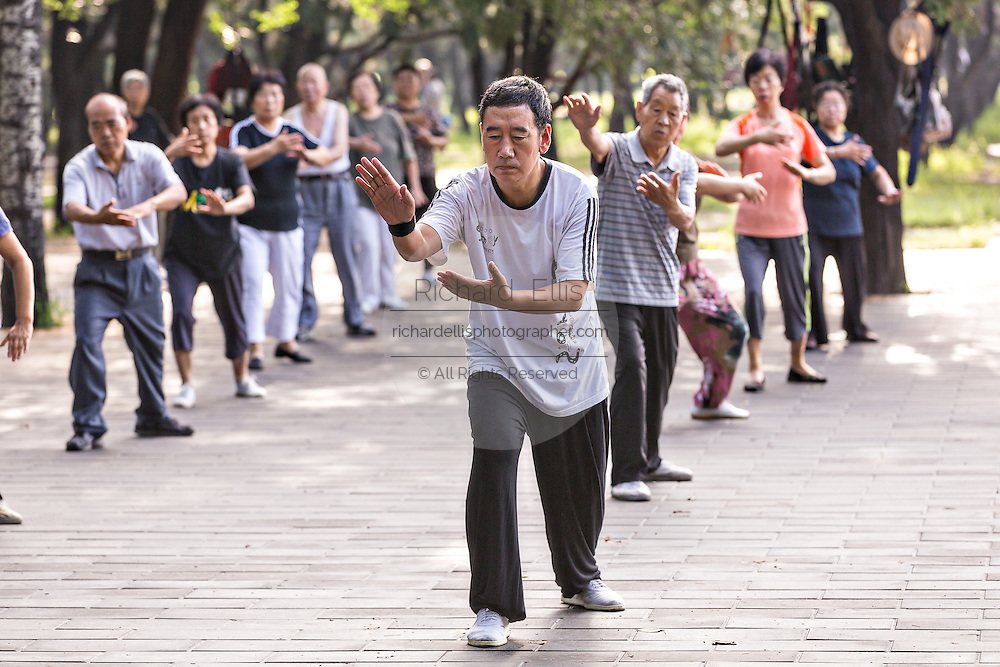 A group of Chinese citizens practice tai chi martial arts exercise early morning at the Temple of Heaven Park during summer in Beijing, China