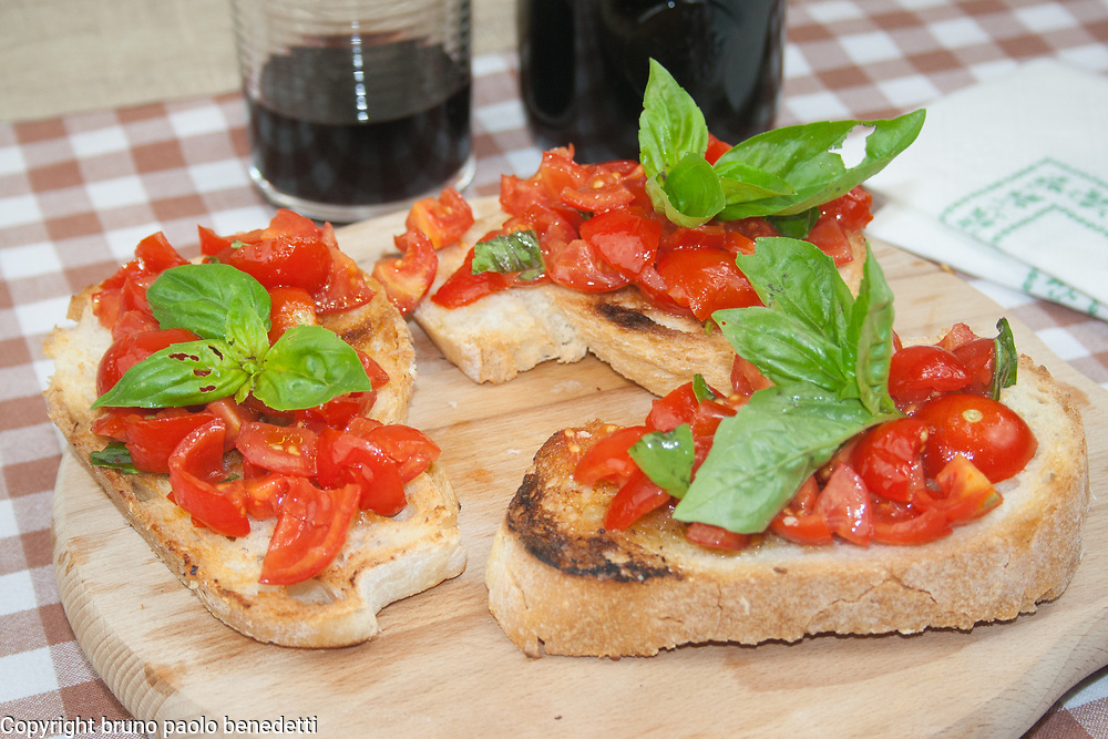 tomato bruschette with basil side view from above close-up on wooden chopping board, italian starter