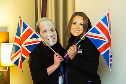 Deputy hotel Manager Nicky Gashtasbi and Assistant Manager Bruna Salvadori try on Duke and Duchess of Cambridge masks and pose with flags left behind by guests. London, July 24 2019.