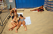 Three girlfriends sunbathe on a sandy Lowestoft beach as a muscular male admirer lies longingly a short distance away