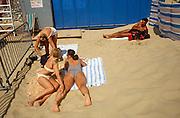 Three girlfriends sunbathe on a sandy Lowestoft beach as a muscular male admirer lies longingly a short distance away