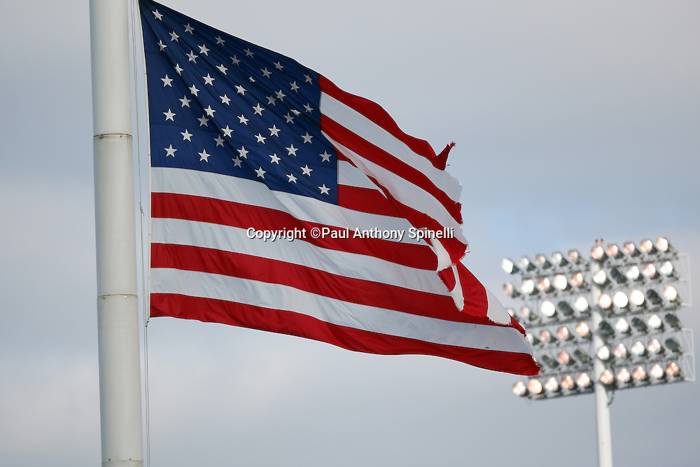 A flag flies in the foreground as stadium lights are lit up for the Buffalo Bills NFL football game against the Houston Texans, November 1, 2009 in Orchard Park, New York. The Texans won the game 31-10. (©Paul Anthony Spinelli)