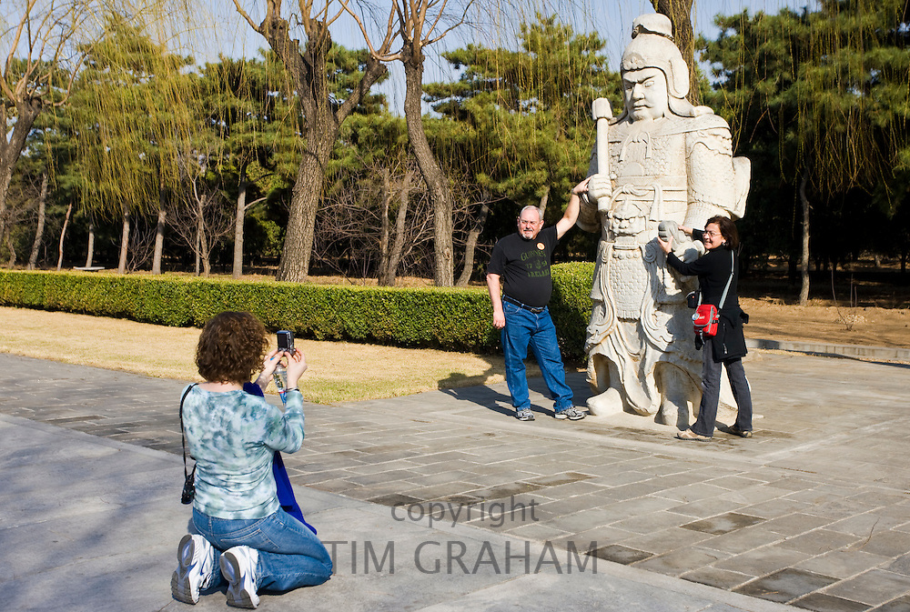 Tourists pose with statue of a military officer on Spirit Way at the Ming Tombs site, Chang Ling, Beijing, China
