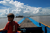 A young Cambodian boy steers a boat full of tourists to the floating village in Tonle Sap Lake. Thousand of young children in Cambodia are forced to work to help their families survive, sometimes in horrific conditions.
