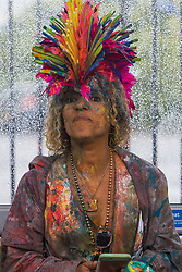 London, August 28th 2016. A reveller takes shelter from the rain in a bus stop as Europe's biggest street party, the Notting Hill Carnival gets underway.