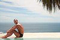 Man sitting at edge of pool ocean in background