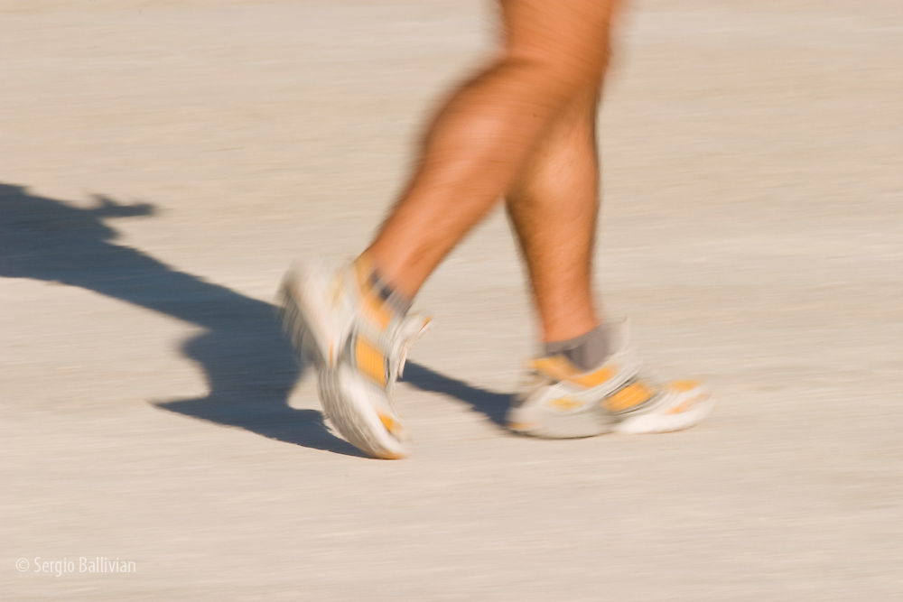 A runner runs on South Beach creating a blurr of colors.