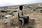 A boy is overlooking the unrecognised village of Wadi el Na'am, pop. 4000, close to Beer Sheva, the capital of the Negev, a large deserted area in the south of Israel.  Wadi el Na'am is located near a large industrial site, Ramat Hovav, and has no infrastructure or electric energy. Water is provided only via storage tanks. It has no health services as the only clinic is deemed illegal and bound to be demolished, as the rest of the structures in the area. Numbering around 200.000 in Israel, the Bedouins constitute the native ethnic group of these areas, they farm, grow wheat, olives and live in complete self sufficiency. Many of them were in these lands long before the Israeli State was created and their traditional lifestyle is now threatened by subtle Governmental policies. The seven Bedouin towns already built are all between the 10 more impoverished towns in Israel.