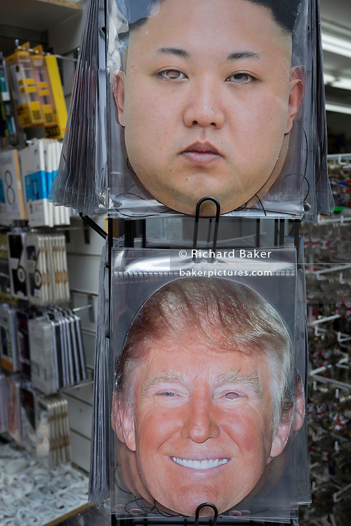 The faces of a serious North Korean leader Kim Jong-un and a smiling US President Donald Trump appear on face masks outside a tourist trinket retailer on Oxford Street, on 1st May, in London, England.