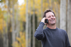 man enjoying a phone call while outside in the woods