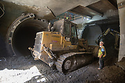 A worker operating a mini excavator carefully pulls down sections of precast concrete tunnel segments and loads them in the bucket of a large bulldozer on the platform level of the station box, where excavation has recently begun.