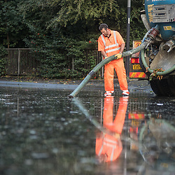 London, UK - 19 September 2014: a workman using a suction pump in reflected in water as torrential rains cause floods and travel disruptions in East London