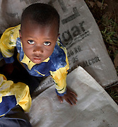 Young boy sitting on empty sugar bags at a UNHCR food distribution centre in the Ghanaian Volta region. Thousands of Togolese citizens crossed the border into Ghana after the violence that followed presidential elections in April 2005. Partly because of strong cultural ties between populations on both sides of the border, Togolese refugees were able to enjoy the relative hospitality of their Ghanaian neighbours, and are today scattered in various villages across the border. The UNHCR complains that, since the refugees aren't concentratred in large camps, media attention has been minimal, and that it has been very difficult to attract funding.