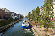 Canal barge in the Canal Saint-Martin, with the Quay de Valmy on the right, seen from the Pont de la rue Eugene Vavin, in the 10th arrondissement of Paris, France. The Canal Saint-Martin is a 4.6km long waterway between the Canal de l'Ourcq and river Seine, built 1802-25 to provide a fresh water source to the city and provide a trade route for canal barges. Picture by Manuel Cohen