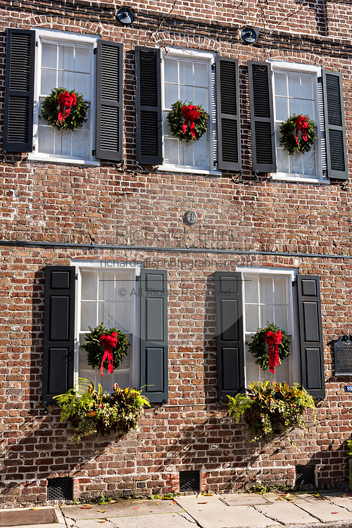Christmas wreaths hang from the windows of a historic home along King Street in Charleston, SC.