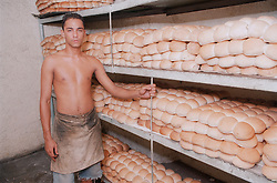 Baker standing next to shelves of bread rolls in bakery in Havana; Cuba,