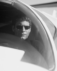 Man wearing sunglasses looking out the cockpit of his small engine plane