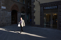 SIENA, ITALY - 20 MARCH 2015: A man walks in the historical center of Siena by a Monte dei Paschi di Siena bank, in Siena, Italy, on March 20th 2015. <br /> <br /> Siena, a Tuscan city and UNESCO World Heritage Site, is home to Monte dei Paschi di Siena, the world's oldest surviving bank and Italy's third largest bank. The bank, founded in 1472, was the largest employer in Siena, and it helped finance a host of community projects and services until it stumbled during the financial crisis started in 2008.
