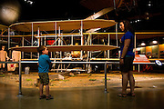 """Katelyn Welker (23) and her nephew, Colin (4), talk about the 1909 Military Flyer built by the Wright Brothers in an exhibit titled """"The Early Years"""" at the National Museum of the Air Force on July 2, 2012 in Dayton, Ohio. (David Welker/www.Turfimages.com)."""