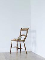 Open book on chair in empty room corner