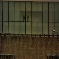 Exterior view of Tate Modern Gallery, London, England with two people meeting.