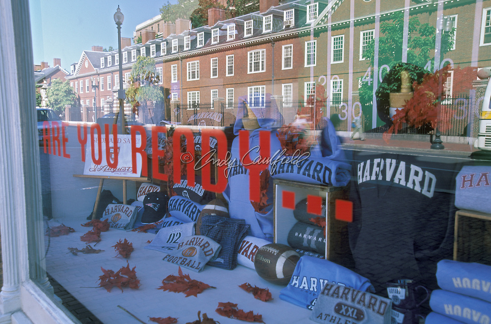 Harvard Square storefont with Harvard clothing in fall leaves and footballs window display.  Harvard University buildings in window reflection. Cambridge, MA.