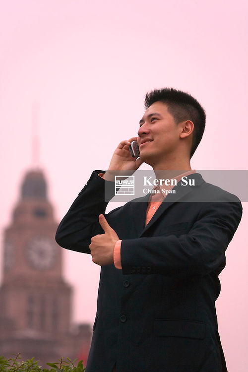 Businessman on cellular phone, colonial building of the Bund in the distance, Shanghai, China