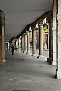 Three shoppers walk under the covered sidewalk in the shopping districe of Valladolid, Spain.