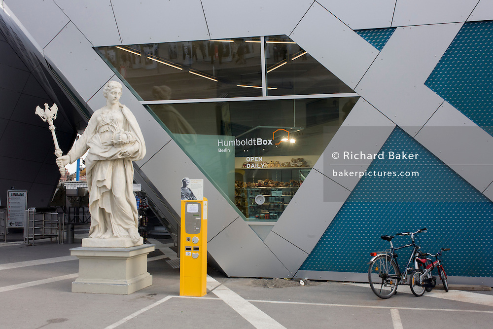 An incongruous landscape of an imperial-style statue from the days of the Weimar Republic, with modern bikes and a tourist information dispenser at Humboldt Box in Berlin Mitte.  .