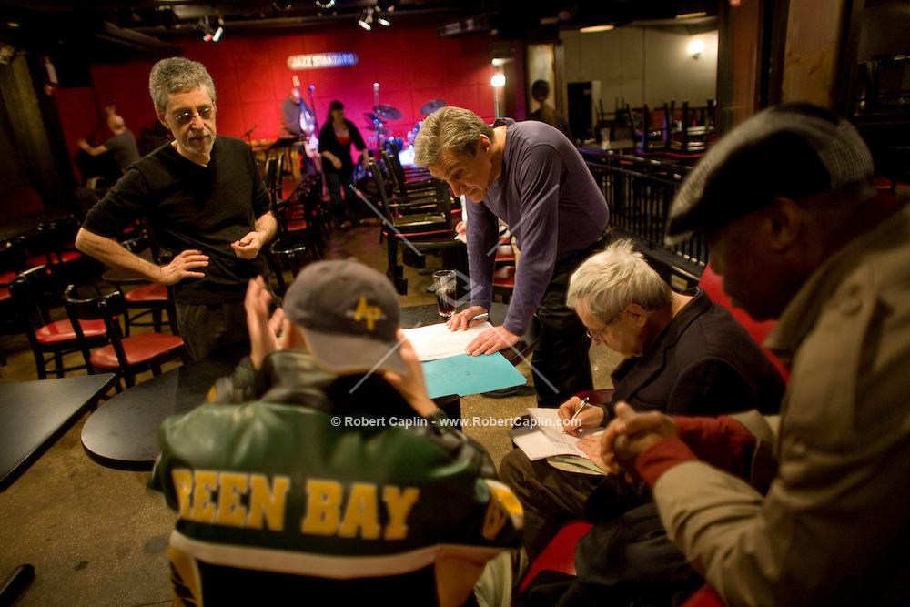 Promoter Milan Simich (Green Bay jacket) and brother of current US poet laureate Charles Simic, white hair, (last names spelled differently) prior to a poetry reading during to a collaboration with jazz musicians and former laureate, Robert Pinsky, purple shirt, at the Jazz Standard in New York, U.S. 1/8/08.