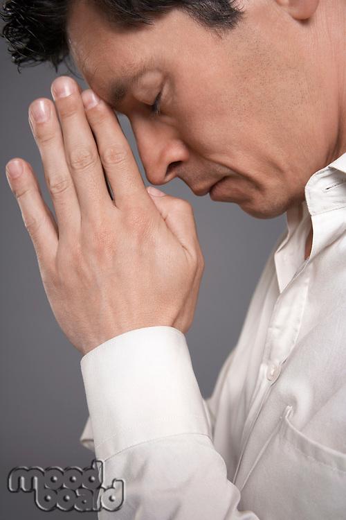 Man in white shirt praying close-up profile